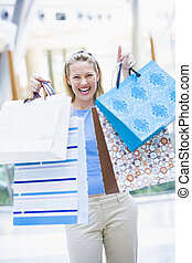 Woman shopping in mall holding bags