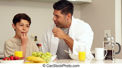 Handsome man having breakfast with his son at home in the...