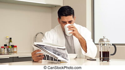 Handsome man drinking coffee and reading newspaper at home...