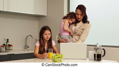 Smiling working mother with her children at breakfast at...