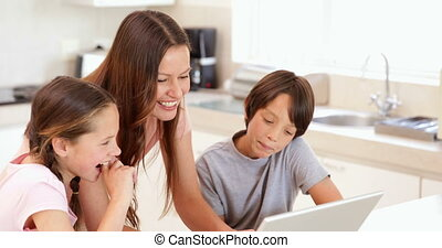 Mother using the laptop with her children