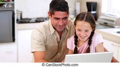 Father using the laptop with his daughter at home in the...