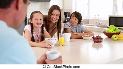 Happy family having breakfast together at home in the...