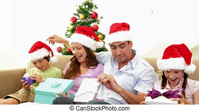 Family opening their christmas presents on the couch at home...