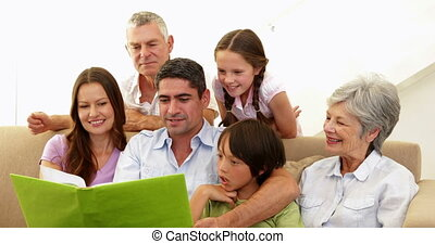 Extended family looking at photo album together at home in...