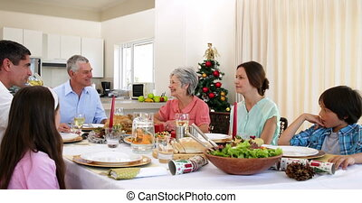 Extended family having christmas dinner together at home in...