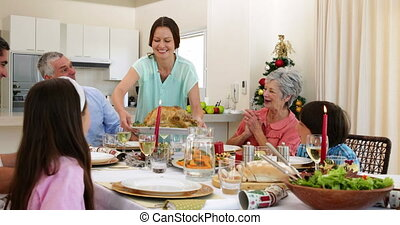 Mother bringing turkey to dinner table for christmas at home...