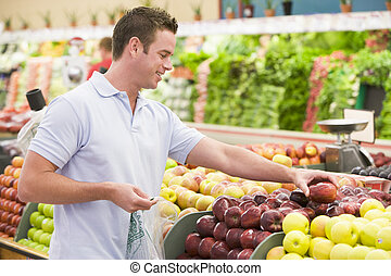 Man shopping in produce section - Man shopping in produce...