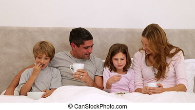 Happy parents and children having breakfast in bed at home...