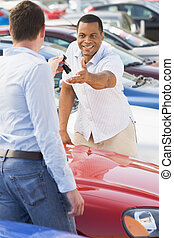 Man collecting new car from salesman