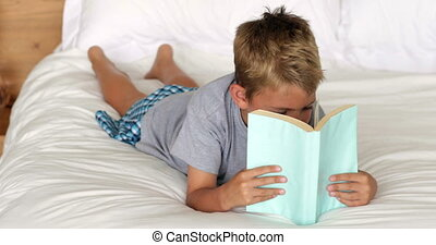 Little boy reading on bed at home in bedroom