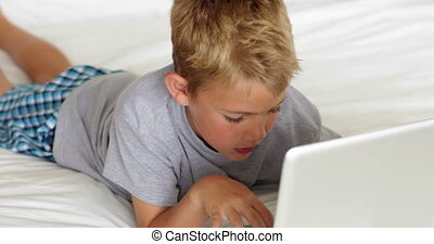 Little boy using laptop on bed at home in bedroom