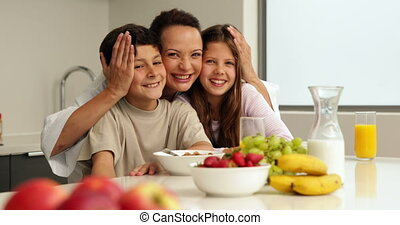 Happy mother with her children having breakfast