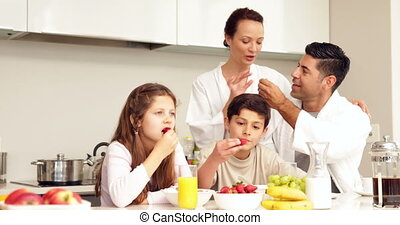 Happy family having their breakfast together at home in the...