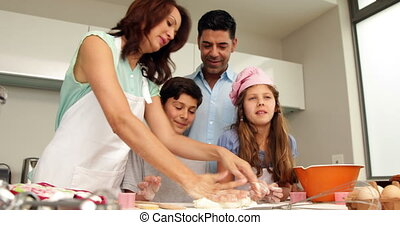 Mother kneading out dough with her family at home in the...