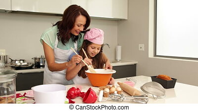Mother showing her daughter how to bake at home in the...