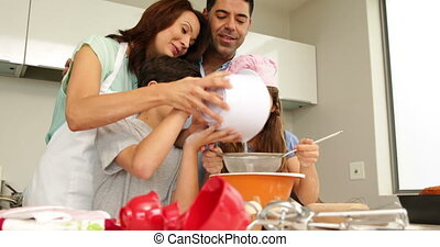 Parents baking with their children at home in the kitchen