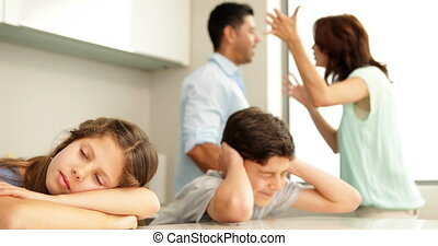 Upset siblings covering their ears while their parents fight...