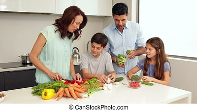Mother showing her children how to chop vegetables at home...