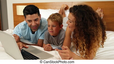 Parents shopping online with their son at home in bedroom