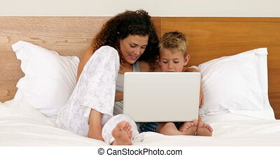 Mother and son using laptop lying on bed at home in bedroom