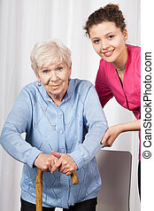 Nurse with elderly woman walking on crutches