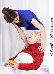 Young woman taking care of grandmother - Young woman taking...