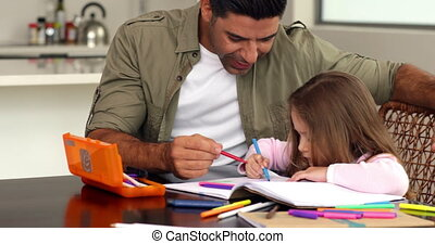 Little girl drawing at the table with her father at home in...