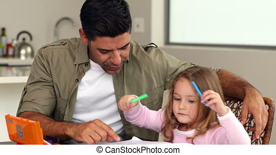 Little girl drawing at the kitchen table with her father at...