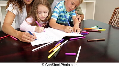 Cute children drawing at the table with their parents at...
