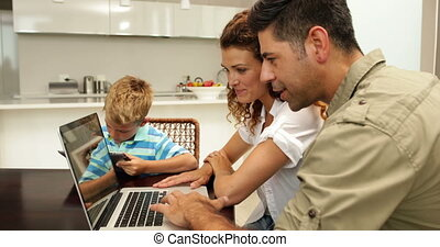 Parents using laptop while their son is drawing at home in...