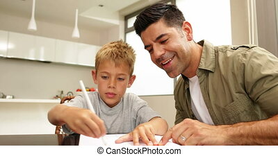 Son drawing with his dad at the table at home in kitchen