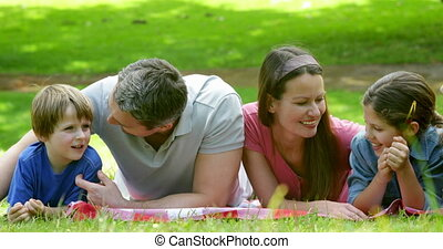 Cute family lying on a blanket in the park and chatting on a...
