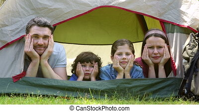 Funny family on a camping trip in their tent on a sunny day...