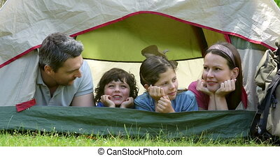 Happy family on a camping trip in their tent on a sunny day...
