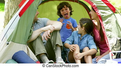 Happy family posing in their tent on a camping trip on a...