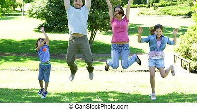 Happy family jumping in the park on a sunny day