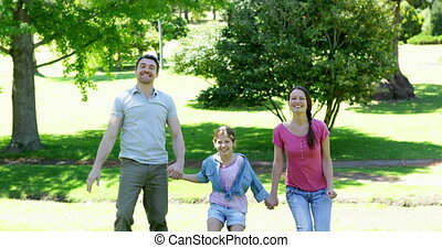 Happy parents and daughter jumping in the park on a sunny...