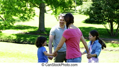 Happy family playing in the park together on a sunny day