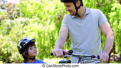 Father and son on a bike ride in the park together on a...