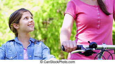 Smiling mother and daughter on a bike ride in the park...