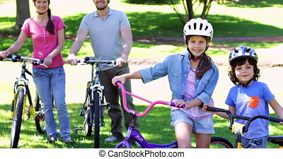 Smiling family on a bike ride in the park together on a...