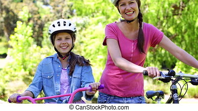 Mother and daughter on a bike ride in the park together on a...