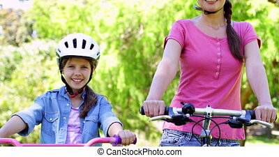 Happy mother and daughter on a bike ride in the park...