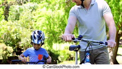 Father and young son on a bike ride in the park together on...