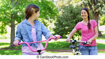 Cute mother and daughter on a bike ride in the park together...