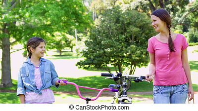 Cheerful mother and daughter on a bike ride in the park...