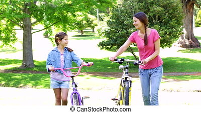 Cute mother and daughter on a bike ride together in the park...
