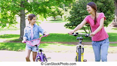 Cute mother and daughter pushing their bikes