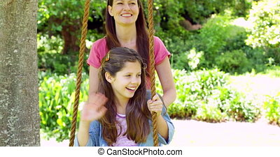 Mother pushing her daughter on a swing